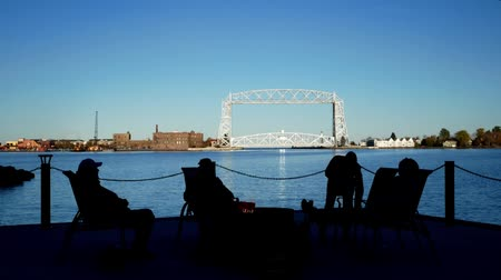 minério : Duluth, MN - October 24, 2018: Friends enjoying a bonfire across the harbor from the Iconic Aerial Lift Bridge on a calm sunny evening under blue skies. Vídeos
