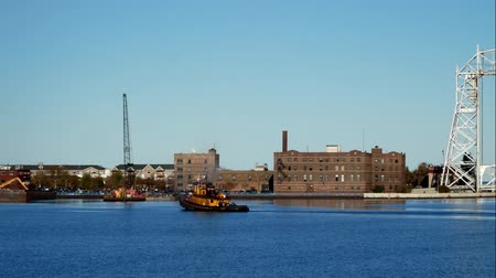 superior : Yellow tug boat sails in Duluth Minnesota Harbor near the iconic aerial lift bridge on a sunny afternoon