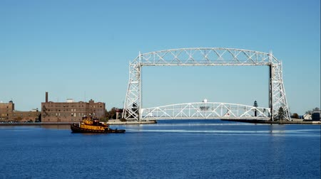 superior : Iconic Duluth Minnesota aerial lift bridge with yellow tug boat in the harbor on a sunny afternoon