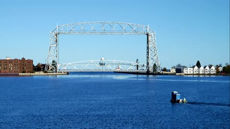 скрестив : Iconic Duluth Minnesota aerial lift bridge with small boat ferrying portable toilets across the harbor on a sunny afternoon