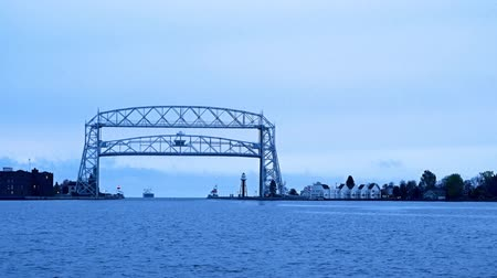 Duluth Minnesota aerial lift bridge raises as iron oar ship approaches from Lake Superior on cloudy morning