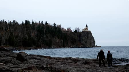 раскол : Senior women exploring shoreline at Split Rock Lighthouse on the north shore of Lake Superior near Duluth and Two Harbors, Minnesota. Стоковые видеозаписи