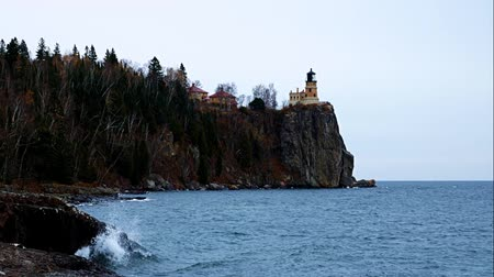 раскол : Waves break on shoreline at Split Rock Lighthouse on the north shore of Lake Superior near Duluth and Two Harbors, Minnesota. Стоковые видеозаписи