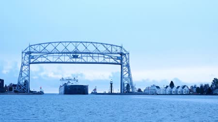 Time-lapse of Iron Ore Ship arriving under Duluth Minnesota aerial lift bridge from Lake Superior on cloudy morning. Стоковые видеозаписи