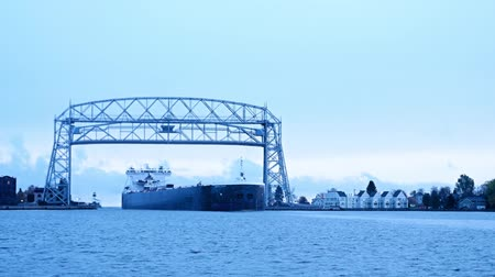 Iron Ore Ship arrives under Duluth Minnesota aerial lift bridge from Lake Superior on cloudy morning.