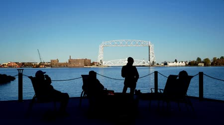 Duluth, MN - October 24, 2018: Friends enjoying a bonfire across the harbor from the Iconic Aerial Lift Bridge on a calm sunny evening under blue skies. Стоковые видеозаписи