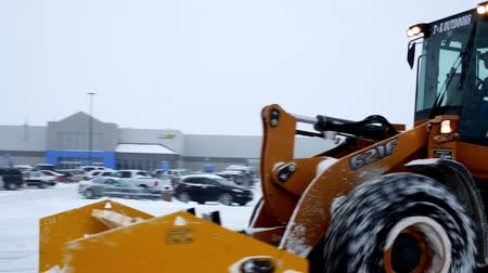 walmart : BEMIDJI, MN - DEC 27, 2018: Snow removal machines clearing Walmart parking lot during storm.