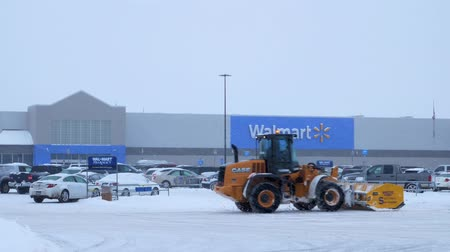 BEMIDJI, MN - DEC 27, 2018: Snow removal machine clearing Walmart parking lot during storm. Stock mozgókép