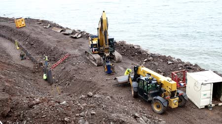DULUTH, MN - October 26, 2018: Caterpillar and construction workers install new pilings to repair weather damage along shore of Lake Superior. 2 clips.