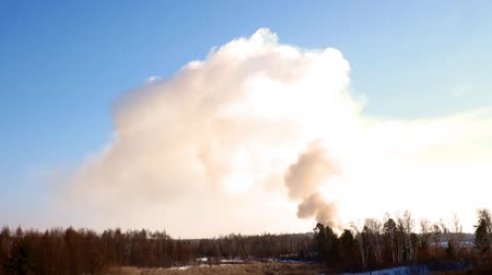 Smoke billowing from a controlled fire at a landfill site in winter in Minnesota on a clear day with blue sky.