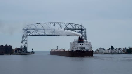 DULUTH, MN - 27 OCT 2019: Ore Ship goes under aerial lift bridge toward Lake Superior on a cloudy autumn day.
