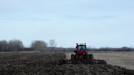 Red farm tractor pulling cultivator turning up black soil on field after harvest of soy beans on autumn day.