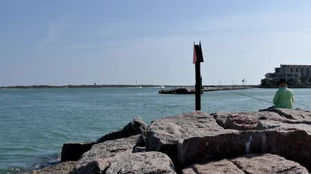 pontoon : PORT ARANSAS, TX - 6 MAR 2016: Fisherman on rocks at marina entrance on a sunny day.