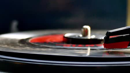 Vinyl Record rotating on retro turntable audio player with focus on needle. Stock mozgókép