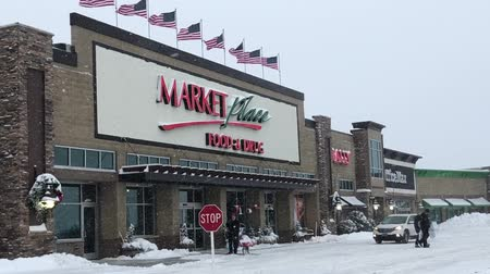 BEMIDJI, MN - 27 DEC 2018: Entrance to Market Place grocery store, Sally, and Office Max during a winter snow storm in northern Minnesota. Stock mozgókép