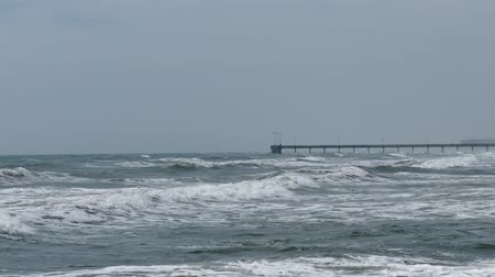 Breaking white waves in a rough sea with a view over the ocean to a distant pier