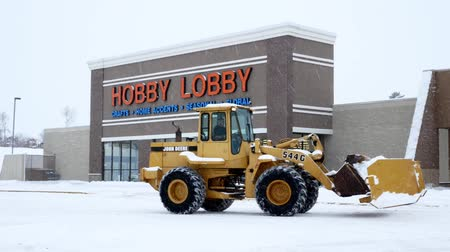 BEMIDJI, MN - 27 DEC 2018: Snow plow in front of entrance to store during a winter storm in Minnesota. Hobby Lobby Craft Store is a corporation which owns a chain of American arts and crafts stores.