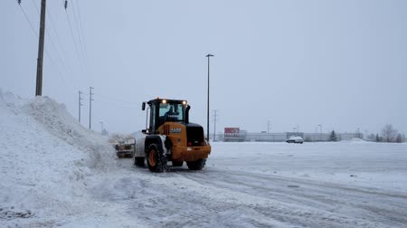 snow plow : BEMIDJI, MN - DEC 27, 2018: Snow removal machine clearing a parking lot during a winter storm.