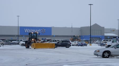 BEMIDJI, MN - DEC 27, 2018: Snow removal machines clearing Walmart parking lot during storm.