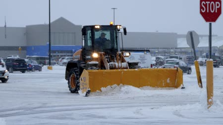 BEMIDJI, MN - DEC 27, 2018: Snow removal machine clearing Walmart parking lot during storm. Стоковые видеозаписи
