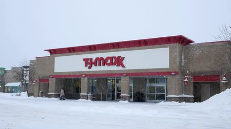 BEMIDJI, MN - 27 DEC 2018: Store front during a winter snow storm with customers and traffic. T.J.Maxx is an American department store chain that sells brand name items for less.