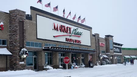бакалейные товары : BEMIDJI, MN - 27 DEC 2018: Entrance to Market Place grocery store, Sally, and Office Max during a winter snow storm in northern Minnesota. Стоковые видеозаписи