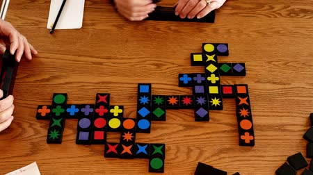 Colors and shapes on tiles placed in rows are played in this game on a wooden table. Time lapse of game being played.
