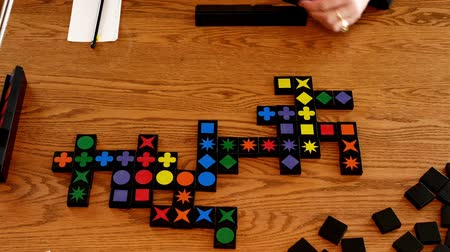 Colors and shapes on tiles placed in rows are played in this game on a wooden table.
