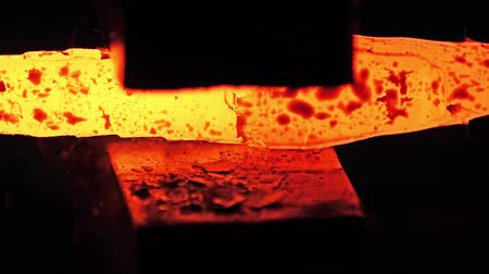 falsificação : Shaping of red hot metal part on the anvil with a jackhammer pneumatic mallet in blacksmith workshop