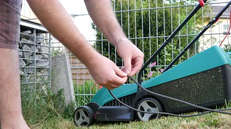 stalk : A man isolates a damaged mower cable.