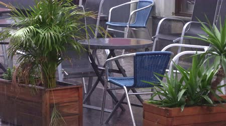 wetness : table in a street cafe in the rain. Stock Footage