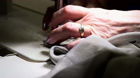 хвоя : seamstress sews on a sewing machine