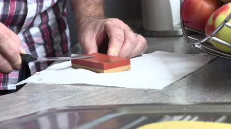 grindstone : The man is sharpening a kitchen knife
