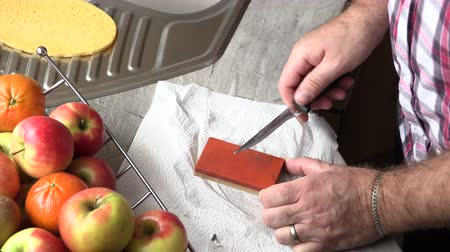 apontador : The man is sharpening a kitchen knife