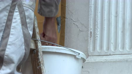 decorador : Painter paints white paint brush wall and roller paint.