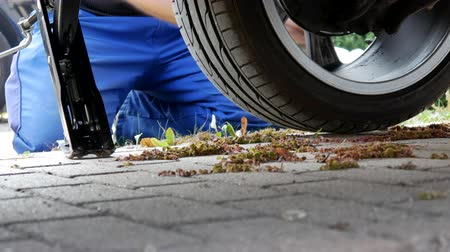 vidalar : A man in work trousers replaces a car wheel,Wheels of summer tires for winter