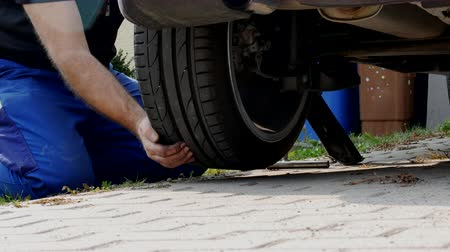kalhoty : A man in work trousers replaces a car wheel,Wheels of summer tires for winter