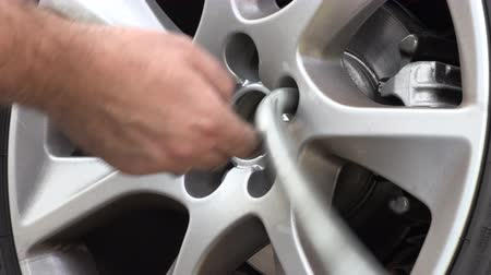 pneumatic : A man in work trousers replaces a car wheel,Wheels of summer tires for winter,Slow Motion Stock Footage