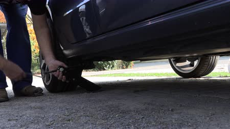 substituição : A man in work trousers replaces a car wheel,Wheels of summer tires for winter,Slow Motion Stock Footage