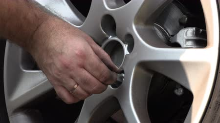 replace : A man in work trousers replaces a car wheel,Wheels of summer tires for winter.