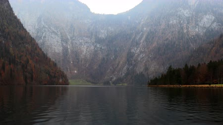 körképszerű : Mountain lake is surrounded by autumn forest, slow motion Stock mozgókép