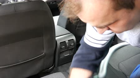 пыль : A man vacuums the car interior, germany