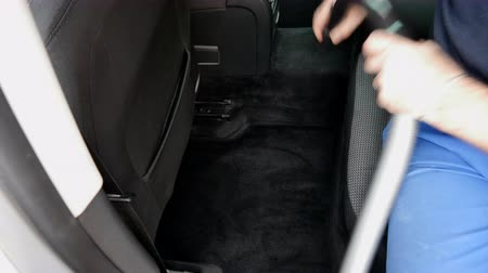 grime : A man vacuums the car interior, germany