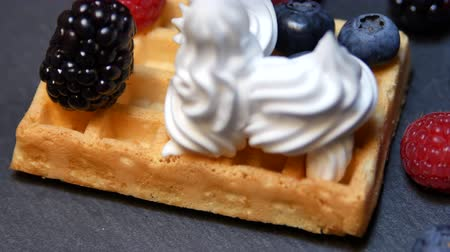 詰め物 : Baked waffles with raspberries, currants and whipped cream. Fresh waffles with whip cream topping on white plate for breakfast