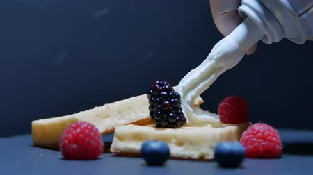 кнут : Baked waffles with raspberries, currants and whipped cream. Fresh waffles with whip cream topping on white plate for breakfast
