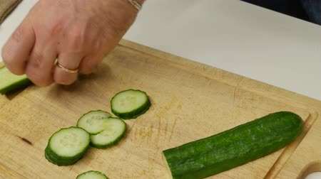 укроп : A man slices cucumbers for salad. Cooking Salad in Home Kitchen. Chefcook are Chopping Slices Cucumber. Hands Sliced Cucumber In Vegan Salad. Стоковые видеозаписи
