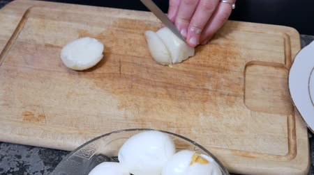boiled egg : Woman cuts boiled eggs for salad