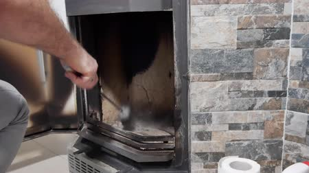 fireside : Man cleans the fireplace from the ash
