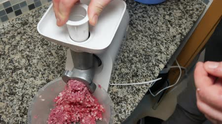cebolas : A man twists pork meat in an electric meat grinder