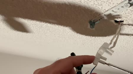 conector : man connects electrical wires from the lamp